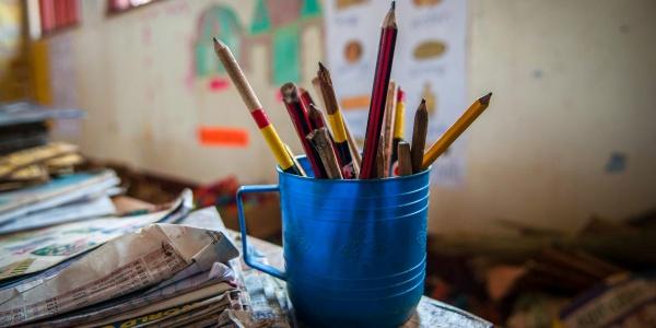 aula di scuola, foto a tazza blu piena di matite colorate