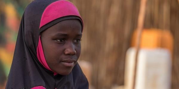 Primo piano di profilo di una bambina africana che indossa un hijab rosa e nero