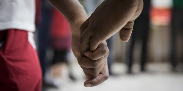 dettaglio di mani che si tengono di un bambino e di un adulto