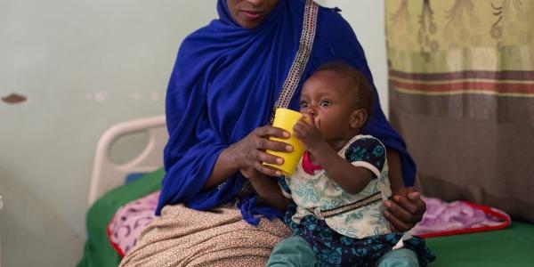 Mamma somala fa bere la figlia dal bicchiere sedute sul letto