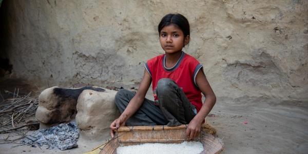 Bambina indiana seduta a terra tiene in mano un contenitore in corda con dentro il riso