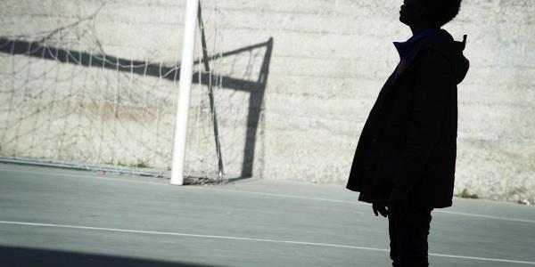Sagoma nera di un bambino migrante in un campo di calcio