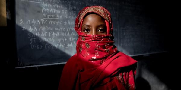 Ragazzina con chador rosso e volto coperto guarda in camera in piedi davanti a una lavagna scritta