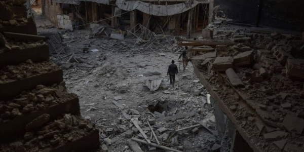 foto dall alto di un quartiere in Siria bombardato, nel sentro un uomo che cammina