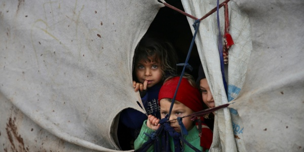 tre bambini siriani sfollati si affacciano dalla fessura di una tenda