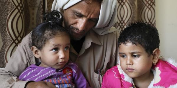 Un papà yemenita con turbante bianco in testa tiene in braccio le sue due bambine e le guarda. Entrambe hanno i capelli corti e neri, una guarda verso l alto e l altra verso la sua sorellina. Indossano magliette viola e rosa