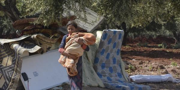 Bambina siriana attraversa campo sfollati con in braccio neonato