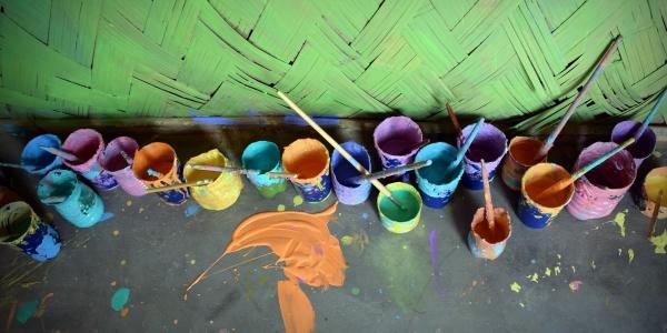 secchi con vernice colorate per terra davanti a un muro verde