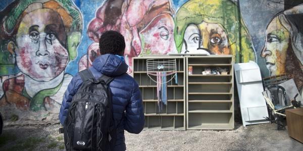 Adolescente di spalle che indossa una giacca pesante blu e tiene sulle spalle uno zaino nero guarda un muro davanti a lui dipinto con un murales e sul muro è appoggiato un mobile con mensole molto rovinato