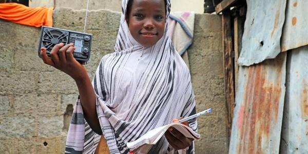bambina vestita di bianco con il velo sul capo tiene tra le mani una radio e una penna e sorride