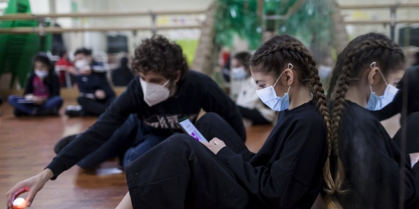una ragazza e un ragazzo vestiti in tuta nera seduti per terra in un aula di danza, indossano mascherina chirurgica per covid-19, lei legge lui gioca con alcuni giochini per terra