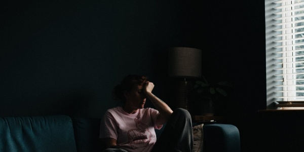 Una donna in una stanza semi buia è seduta sul divano e ha la testa appoggiata alla mano con un aria molto afflitta