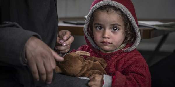 primo piano bambina siriana con cappotto e cappuccio rosso in testa stringe orsacchiotto appoggiata alla gamba di un adulto