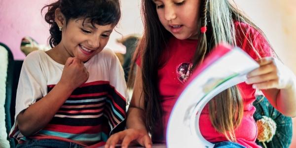 due bambine leggono insieme un libro. Una con i capelli castano scuro raccolti e l'altra con i capelli castano chiaro sciolti.