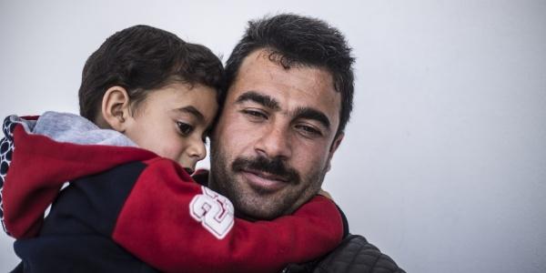 Primo piano papà tiene in braccio suo figlio