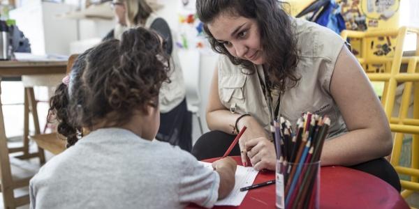 operatrice seduta a un piccolo banco della scuola dellinfanzia con una bimba mentre colorano insieme