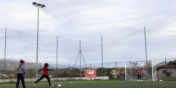 campetto di calcio con due bambini che giocano in lontananza, uno con maglietta rossa e pantaloni neri l altro con maglietta grigia e pantalone nero