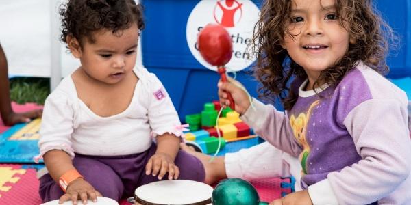 due bimbe piccole sedute per terra su un tappetino giocano con degli strumenti musicali per bimbi
