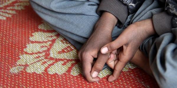 primo piano di mani di un bambino seduto a terra a gambe incrociate su un tappetino