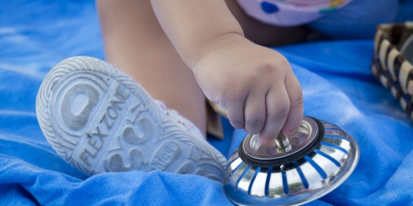 bambina molto piccola seduta su un telo blu gioca con un oggetto che tiene in mano. Nell inquadratura si vedono solo la mano e il piedino