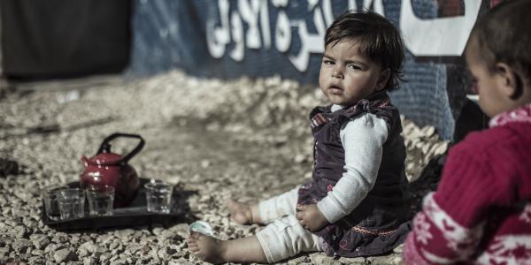 Bambina in Libano seduta per terra a piedi nudi e con lo sguardo triste
