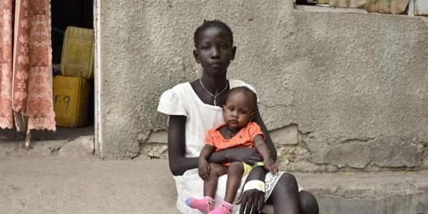 Una ragazzina sud sudanese seduta sui gradini davanti casa sua tiene in braccio una bambina piccola vestita di rosso.