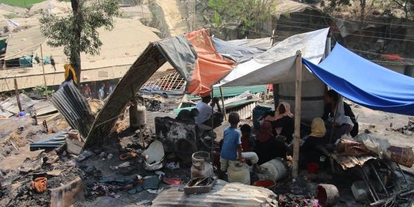 Tenda di fortuna nel mezzo di cenere e resti incendiati nel campo di coxs bazar in bangladesh. Sotto la tenda si ripara una famiglia Rohingya di varie persone