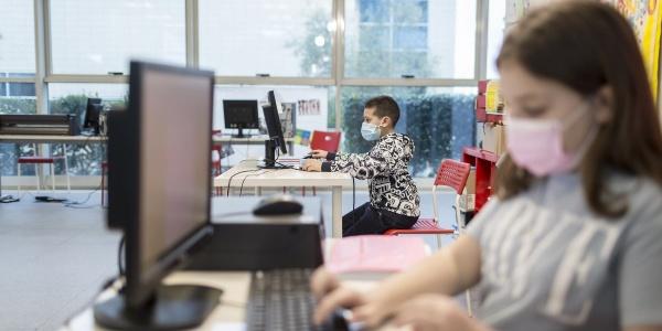 Una bambina di profilo in primo piano sfocata scrive al pc ed e seduta a un tavolo. Al suo lato si vede un altro bambino seduto alla scrivania intenti a scrivere al pc.