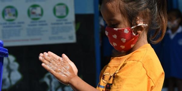bambina indonesiana di profilo si lava le mani mentre indossa mascherina colorata sul viso.