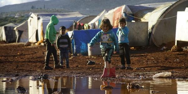 Un gruppo di bambini siriani, quattro in tutto, sono ripresi in piedi da lontano all interno di un campo profughi e su un terreno infangato a causa delle piogge. In particolare, una bambina con stivaletti rosa avanza camminando verso una grande pozzanghera d acqua di fronte a lei.
