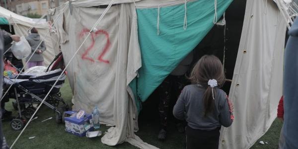 bambina di spalle di fronte a una tenda in accampamento di risposta al terremoto in Albania