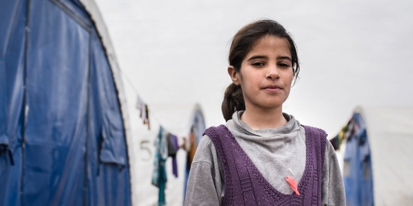 bambina irachena di circa 12 anni è accanto a una tenda di un campo rifugiati, è ripresa a mezzo busto e indossa una felpa grigia e viola. I suoi capelli sono castani e legati in una coda