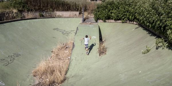 Bambino di spalle e in lontananza corre sulla salta di una pista da skate abbandonata
