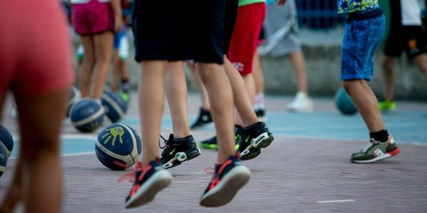 Primo piano di gambe di bambini e bambine che giocano con la palla in un campo da basket