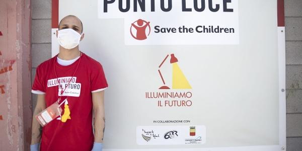 Un operatore save th children posa davanti al cartello di ingresso del Punto Luce di Napoli Barra.