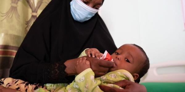 Una donna somala con tunica nera indossa mascherina ed è seduta su un letto. Sulle sue gambe tiene il figlio che ha una tutina gialla e lo imbocca facendogli mangiare cibo terapeutico.