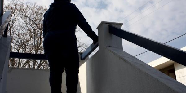 Sagoma di una bambina in cima a delle scale che sta in piedi e appoggia il braccio sulla balaustra.
