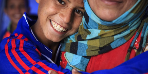 Ragazzo sorridente abbraccia la sua mamma