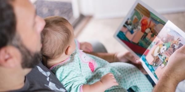 bimba neonata in braccio al papà mentre leggono insieme un libro illustrato