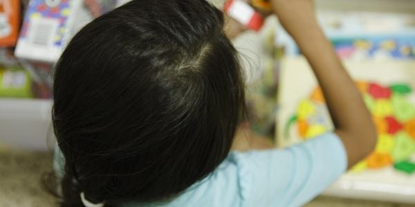 Bambina di spalle presa dall alto mentre gioca con qualcosa in mano. Sullo sfondo un foglio colorato