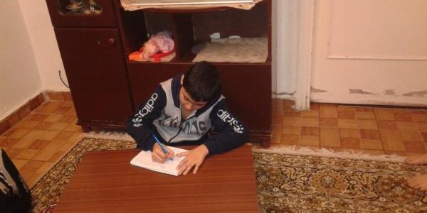 Bambino libanese di circa 12 anni è seduto a terra su un tappeto e scrive su un figlio bianco appoggiato a una tavolo di legno.