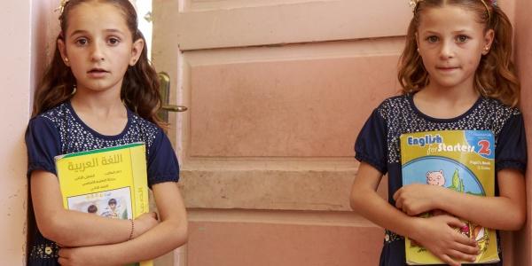 due bambine bionde in piedi davanti a una porta con un libro in mano