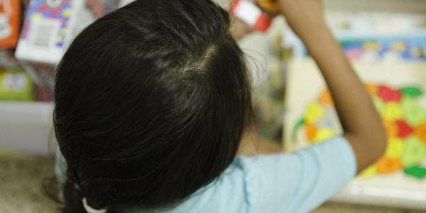 Bambina con capelli nera presa dall alto. Si vede la testa con i capelli neri raccolti in una cosa e una maglietta celeste chiaro.