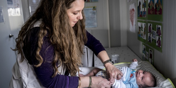 Mamma cambia pannolino a bambino su fasciatoio