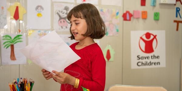 bambina in classe, in piedi, mentre legge ad alta voce qualcosa da un foglio. Sullo sfondo la parete dell aula è ghermita di disegni dei bambini e delle bambine.
