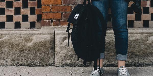gambe di una studentessa che tiene in mano uno zaino nero. Sullo sfondo muro di mattoncini