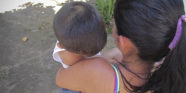 Donna mora di spalle tiene in braccio bambino piccolo