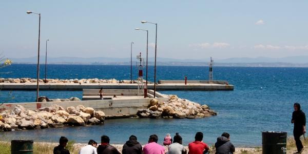 bambini migranti di spalle seduti davanti al mare