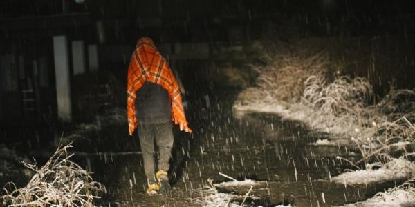 Foto notturna in un viale oscuro mentre sta nevicando. Si vede di spalle un ragazzo che cammina lungo il viale e sotto la neve con pantaloni scuri e una coperta arancione posta sopra le spalle e la testa.