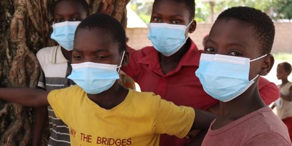 Tre bambini mozambicani appoggiati ad un albero indossano le mascherine e magliette giallo rosse e rosa e guardano verso la loro destra